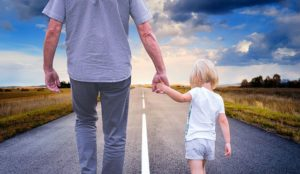 father walking with daughter on empty road