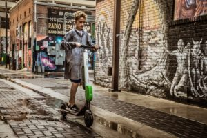 kid riding lime electric scooter